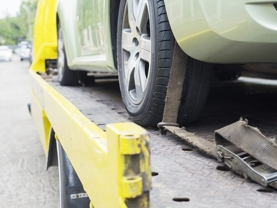 Green Car Strapped To a Yellow Flatbed Tow Truck