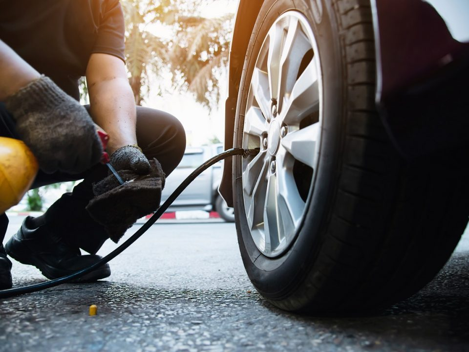 Technician inflating car tire as part of maintenance service